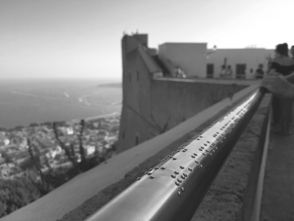 Imagine cu balustrada în prima plan pe care se văd în relief caracterele în Braille. pe fundal se vede în ceață orașul.